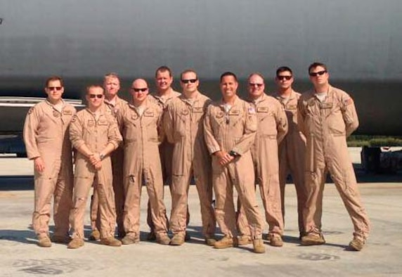 Crew members, slated to receive the 2013 Earl T. Ricks award pose in front of a C-5 Galaxy April 19, 2013. During an overseas mission the aircraft struck multiple birds during takeoff. Two engines were damaged but the crew manged to return the aircraft safely to the airfield.