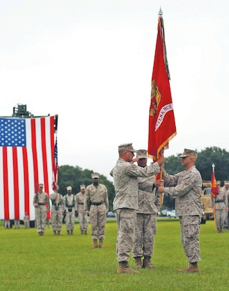 Col. Stephen A. Medeiros, right, relinquishes command of Marine Depot Maintenance Command to Col. Jeffrey Q. Hooks during a change-of-command ceremony Aug. 1 at Boyett Park aboard Marine Corps Logistics Base Albany.
