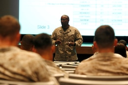 Sgt. Maj. Mark A. Byrd explains proper fitness report procedures to more than 45 Marines during the Manpower Management Support Branch Promotion and Performance brief at the base theater here Aug. 7. The brief covered information to assist Reporting Seniors and Reviewing Officers with completing fitness reports, as well as help Marines receiving reports better understand how they are evaluated. Byrd is the sergeant major for the Performance Evaluation Section at Headquarter Marine Corps.