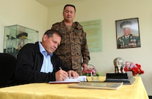 Dr. Peter R. Lavoy, Acting Assistant Secretary of Defense for Asian and Pacific Security Affairs, signs the visitor/memoribilia book in the Honorary Room for Mongolian Armed Forces Maj. Gen. Guriin Ragchaa at the United Nations compound in the Tavan Tolgoi (Five Hills) training area, Aug.6. Approximately 1,000 service members from 13 different nations are participating in the exercise, with  both the command post exercise (CPX) and field training exercise (FTX) at Five Hills Training Area in Mongolia, both focusing on peacekeeping and stability operations. Dr. Lavoy toured the area to meet with exercise participants and leadership from Mongolia, U.S. and other participating nations. U.S. Marine Corps Forces Pacific is the executive agent for Khaan Quest 2013.