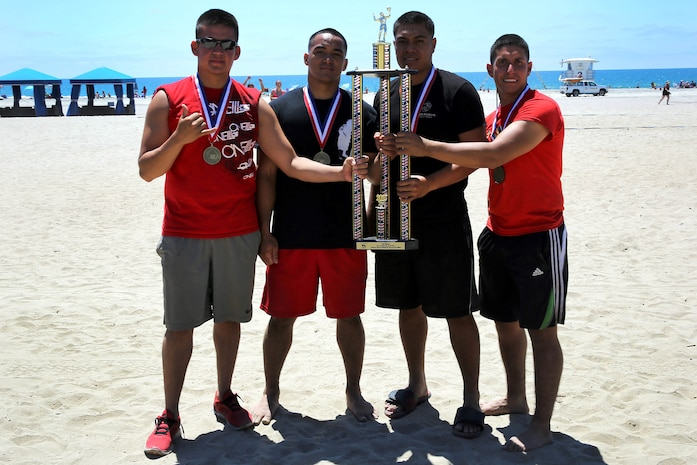 Team USO wears their first place medals and hold their championship trophy after defeating the Naval Hospital Islanders in the title game during the Commanding Generals Cup, 4-Person Beach Volleyball Tournament held at Del Mar Beach Resort here August 7. The Marines in Team USO are from 1st Light Armored Reconnaissance Battalion here. The tournament is an annual event and had over 120 Marines and sailors in attendance.