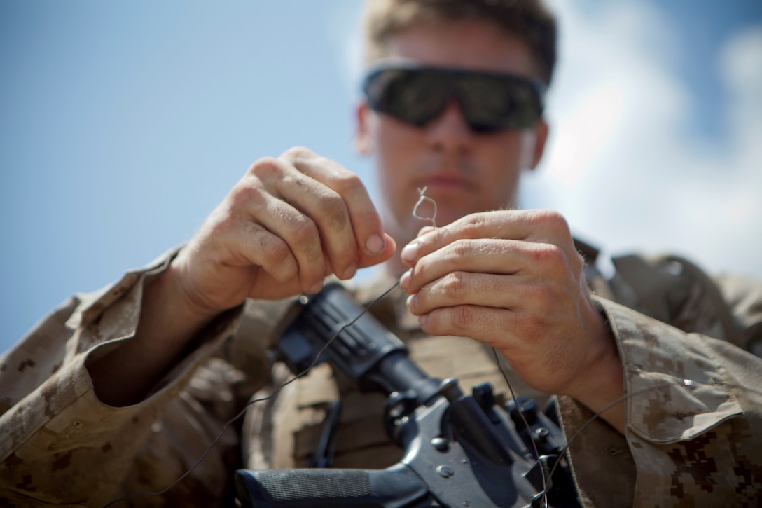 """Cpl. Benjamin Brannon, a combat engineer with 2nd Combat Engineer Battalion and a student in the Sapper Leadership Course, connects wires to explosives during rehearsal for a demolition range aboard Marine Corps Base Camp Lejeune, July 22, 2013.  The method of connection, called """"Western Union Pigtail Splice,"""" was one of many ways to prepare a charge the students of the Sapper course learned."""