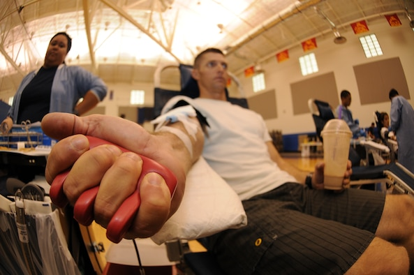 Master Sgt. Christopher Thorne, 734th Air Mobility Squadron air transportation manager, squeezes his hand to increase the blood flow through his veins at an Armed Services Blood Program blood drive Aug. 7, 2013, on Andersen Air Force Base, Guam. Guam's ASBP Donor Center conducts a blood drive at the Coral Reef Fitness Center monthly. (U.S. Air Force photo by Airman 1st Class Emily A. Bradley/Released)