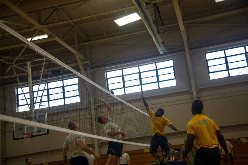 An Airman from the 437th Aerial Port Squadron jumps to spike volleyball against Navy Sailors during a match Aug. 2, 2013, at the Fitness Center on Joint Base Charleston, S.C. (U.S, Air Force photo/Tech. Sgt. Douglas)