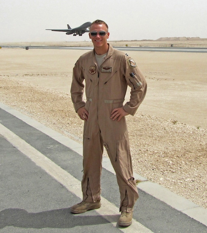 U.S. Air Force Capt. Dustin Willard poses for a photo on the flightline while a B-1 Bomber takes off in the background. Willard served as the aircraft commander of Bone-34, which was named the Air Force's 2012 bomber crew of the year and was awarded with the Air Force Association's Gen. Curtis E. LeMay Award. (Courtesy photo)