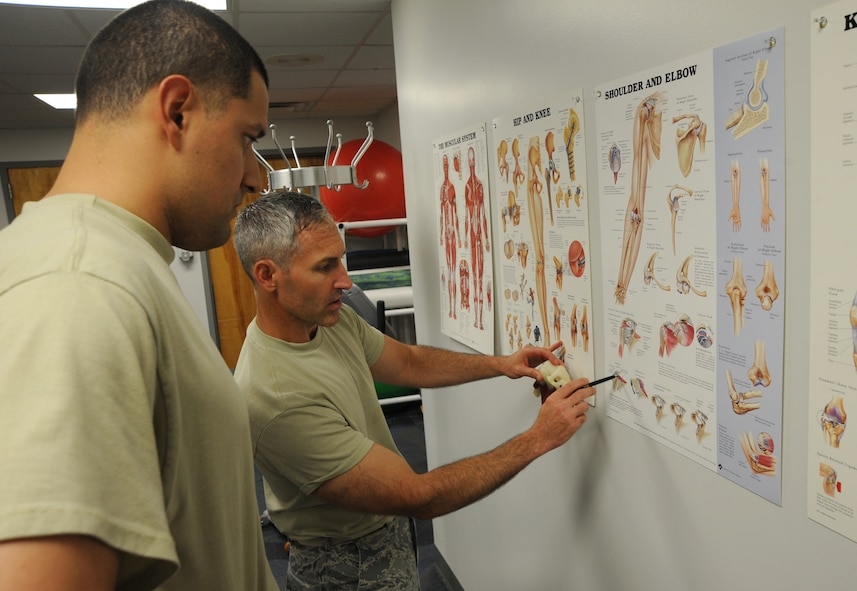 U.S. Air Force Maj. Michael Holmes, 509th Medical Operations Squadron physical therapy technician, reviews a chart with U.S. Air Force Staff Sgt. Tim Ferguson, 509th Maintenance Group command chief assistant, to explain the diagnosis of his injury at Whiteman Air Force Base, Mo., Aug. 6, 2013. The physical therapy clinic uses a variety of methods in providing evaluations, such as joint manipulation and mobilization, electrical stimulation, taping and bracing, and ultrasounds.  (U.S. Air Force photo by Airman 1st Class Bryan Crane/Released)