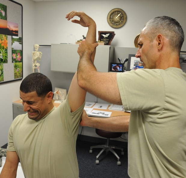 U.S. Air Force Maj. Michael Holmes, 509th Medical Operations Squadron physical therapy technician, stretches the shoulder of U.S. Air Force Staff Sgt. Tim Ferguson, 509th Maintenance Group command chief assistant, during an initial physical therapy evaluation at Whiteman Air Force Base, Mo., Aug. 6, 2013. The physical therapy clinic employs a variety of methods in providing evaluations, such as joint manipulation and mobilization, electrical stimulation, taping and bracing, and ultrasounds. (U.S. Air Force photo by Airman 1st Class Bryan Crane/Released)