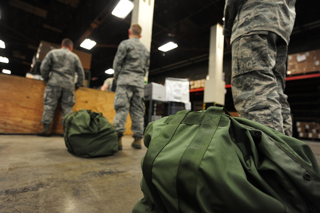 U.S. Air Force Airmen wait in line for assistance with chemical gear before participating in chemical, biological, radiological and nuclear (CBRNE) training at Whiteman Air Force Base, Mo., July 29, 2013. This training builds upon the CBRNE computer-based training, and enables Airmen to acquire hands-on experience by creating real-world scenarios designed to test their knowledge and skills when it comes to responding to CBRNE incidents. (U.S. Air Force photo by Staff Sgt. Nick Wilson/Released)