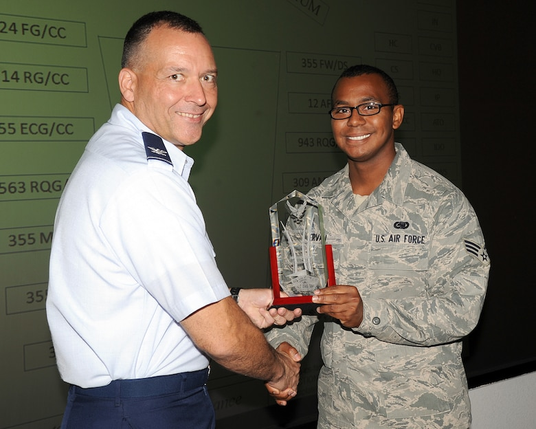 U.S. Air Force Col. Kevin Blanchard, 355th Fighter Wing commander, presents Senior Airman Sammie Ervan, 355th Logistics Readiness Squadron base support plan manager, the Air Force level Logistics Readiness Airman of the Year award at Davis-Monthan Air Force Base, Ariz., Aug. 6, 2013. SrA Ervan recieved the award for the year of 2012. (U.S. Air Force photo by Senior Airmen Timothy Moore/released)