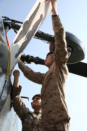 Lance Cpl. Jordan Matting, a corrosion control technician with Marine Aviation Logistics Squadron 31, left, and Sgt. Robert Wilkes, the noncommissioned officer-in-charge of the MALS-31 corrosion control facility, right, places graphics of Navy warfare devices in honor of Hospitalman 1st Class Kevin Frank, July 29.