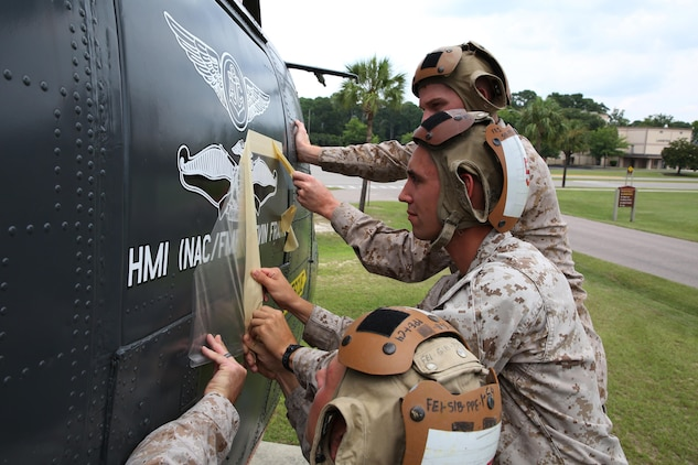 Marines with Marine Aviation Logistics Squadron 31, places graphics of Navy warfare devices in honor of Petty Officer 1st Class Kevin Frank, July 29.