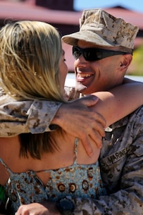 Lieutenant Col. Vincent Laratta, regimental judge advocate, Regimental Combat Team 7, and a native of Denver, embraces his wife Dione for the first time in approximately 10 months aboard Camp Margarita here, Aug. 7. Family and friends waited for the Marines as they arrived at Camp Pendleton. The servicemembers worked with Afghan forces while deployed to Southwest Afghanistan.