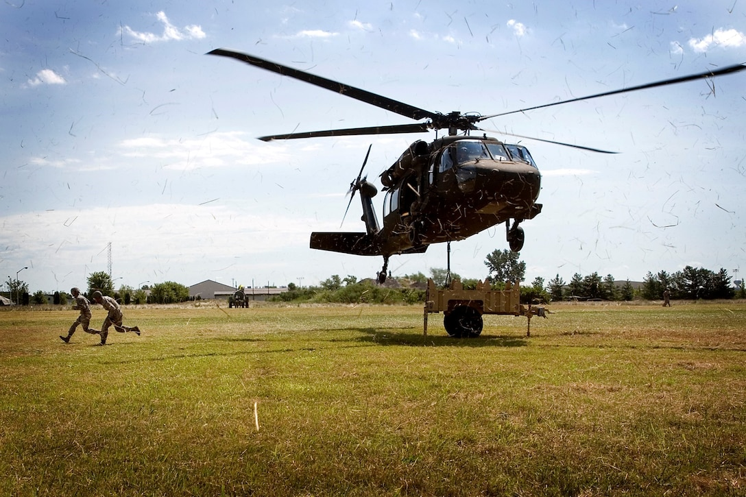 Reservists assigned to the 434th Force Support Squadron make their way from under an Army Reserve UH-60 Black Hawk after hooking a small trailer to the hovering helicopter for transport during a joint training exercise July 23, 2013, at Grissom Air Reserve Base, Ind. (U.S. Air Force photo/Tech. Sgt. Douglas Hays)