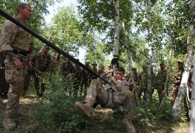 Cpl. Justin Haish, an instructor for the Khaan Quest 2013 survival course and member of the Jungle Warfare Training Center in Camp Gonsalves, Okinawa, Japan, dismounts during a rope corral demonstration for Mongolian Armed Forces soldiers and U.S. Marines, Aug. 7. Khaan Quest is a peacekeeping operations-focused, combined training event between U.S. Marine Corps Forces Pacific, U.S. Army Pacific, and the MAF. MARFORPAC and USARPAC have conducted similar training with MAF since 2003, and this exercise marks the 11th iteration of Khaan Quest. Military personnel from Australia, Canada, France, Germany, Japan, India, Nepal, Republic of Korea, Tajikistan, United Kingdom and Vietnam are also participating in the exercise. Haish, currently part of the unit deployment program with Kilo Company, 3rd Battalion, 3rd Marine Regiment, is from Kailua, Hawaii.