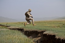 U.S. Marine Lance Cpl. Nicholas Moore with 3rd Battalion, 3rd Marine Regiment, 3rd Marine Division jumps over a ditch during a cordon and search lane ledt by members of the Mongolian Armed Forces, Australian Army South Korean Army and U.S. Soldiers and Marines at Five Hills Training Area, Mongolia on Aug. 08, 2013. Khaan Quest is an annual multinational exercise sponsored by the U.S. and Mongolia, and it is designed to strengthen the capabilities of U.S., Mongolian and other nations' forces in international peace support operations.