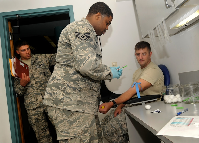 Oregon Air National Guard Staff Sgt. Clifton Matthews, 142nd Fighter Wing Medical Group, prepares to take a blood samples from Staff Sgt. Rockney Schock, (right) and Senior Airmen Benjamin Courtney (left), 142nd Fighter Wing Security Forces Squadron, as part of the in processing procedures at the Portland Air National Guard Base, Ore., Aug. 9, 2013.  (Air National Guard photo by Tech. Sgt. John Hughel, 142nd Fighter Wing Public Affairs/released)