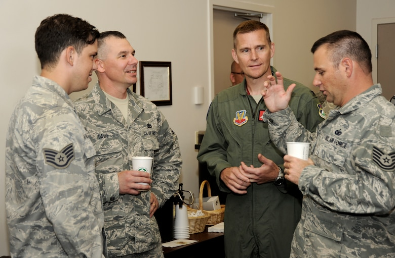Oregon Air National Guard Col. Rick Wedan, 142nd Fighter Wing Commander (center-right) listens to Tech. Sgt. Daniel Mace (far-right), Staff Sgt. James Kalmback (left) and Tech. Sgt. Steven Davis (center-left) of the 142nd Fighter Wing Security Forces Squadron, during an in processing USO event held at the Portland Air National Guard Base, Ore., Aug. 9, 2013. (Air National Guard photo by Tech. Sgt. John Hughel, 142nd Fighter Wing Public Affairs/released)