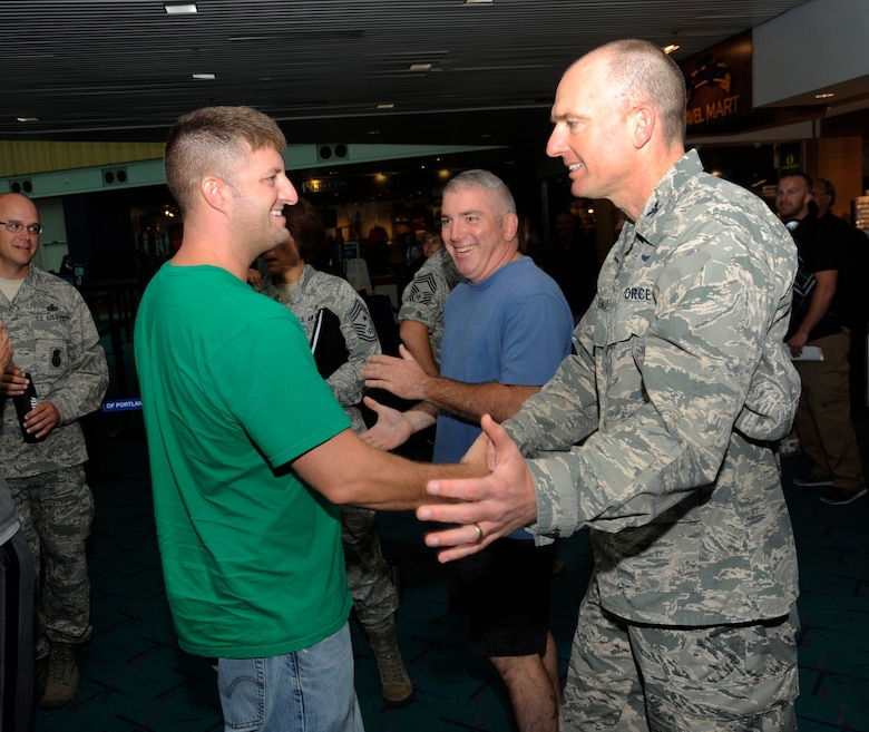 Members of the 142nd Fighter Wing Security Forces Squadron are welcomed back to Oregon at the Portland International Airport after their recent deployment, Aug. 8, 2013. A total of 26 Airmen from the 142nd Fighter Wing spent six months in Qatar in support of Operation Enduring Freedom. (Air National Guard photo by Tech. Sgt. John Hughel, 142nd Fighter Wing Public Affairs/released)