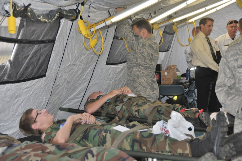 Airman from the 139th Aeromedical Evacuation Squadron of the 109th Airlift Wing, while working with civilian agencies, provide treatment during an exercise to simulated patients, Civil Air Patrol cadets, after they were brought to the base from the Aplaus Fire Department, Aug. 8, 2013. This exercise highlighted the vital function of the 109AW and 139AES in the National Disaster Medical System and homeland defense mission as well as the cooperation and coordination between the 109AW and New York state civilian medical and emergency management assets. (U.S. Air National Guard photo by Master Sgt. William M. Gizara/Released)