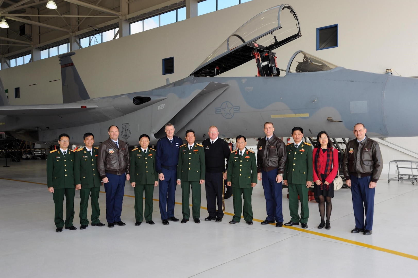 A delegation from Vietnam joins Oregon National Guard leadership for a photo in front of an F-15 Eagle during a visit to the Oregon Air National Guard's 142nd Fighter Wing at the Portland Air National Guard Base, April 15, 2013.