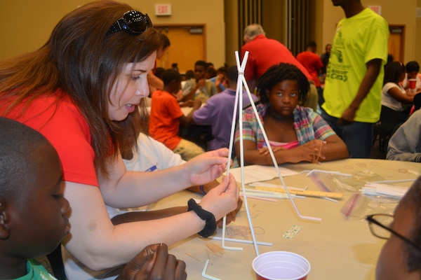 Civil engineer Jessamyn Fluitt, Engineering Division, assists students with the water tower construction at the one-day STEM event at the University of North Florida.