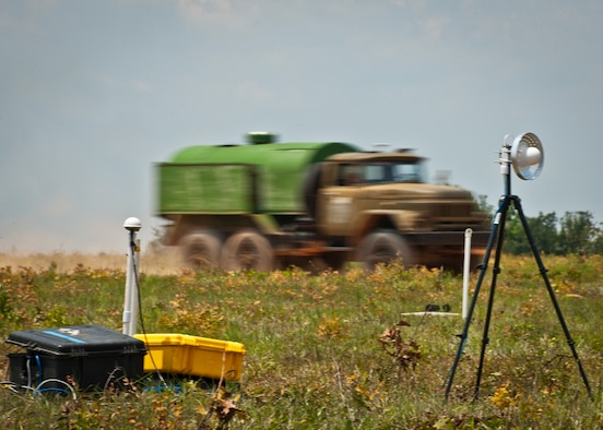 A military vehicle rushes by recording equipment set up to collect all sound data emitted from