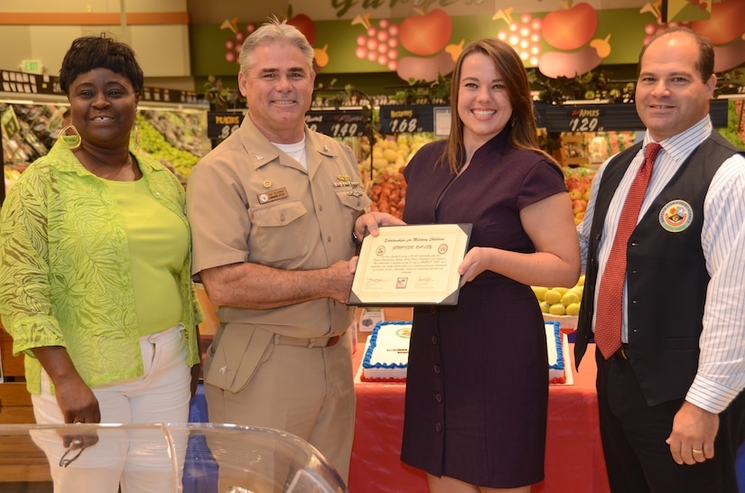 JOINT BASE CHARLESTON - WEAPONS STATION, S.C. — Naval Support Activity Charleston Commanding Officer Capt. Timothy Sparks, Earlene Mills, Weapons Station commissary store manager and Thomas Mundinger, assistant store director present the Scholarship for Military Children to Jennifer Bailey, daughter of JB Charleston deputy commander Navy Capt. Thomas Bailey and Janet at the Weapons Station commissary Aug. 1, 2013. The $1,500 scholarship is one way the Defense Commissary Agency and Fisher House contribute back to the military community. (U.S. Navy photo/ Petty Officer 1st Class Chad Hallford)