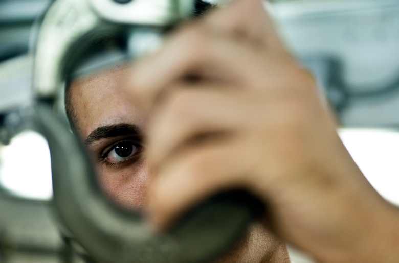 Airman 1st Class Giovanni Costanza, 39th Maintenance Squadron technician, closely scrutinizes a hook during his day-to-day operations Aug. 2, 2013, at Incirlik Air Base, Turkey. Costanza is a native of Hammond, La. and a first-term Airman at Incirlik AB. (U.S. Air Force photo by Senior Airman Daniel Phelps/Released)