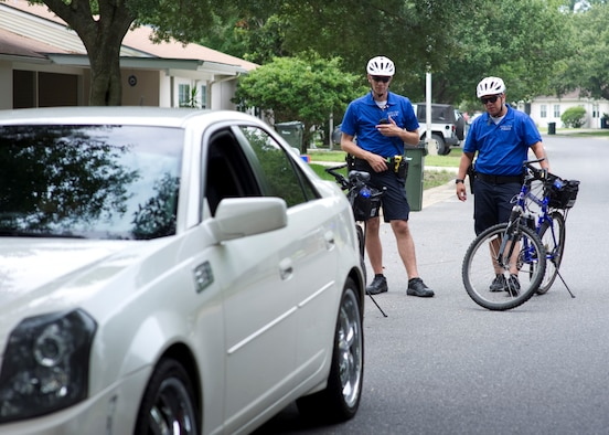 Airman 1st Class Gary Jackson and Senior Airman Pablo Uribe, bike patrolmen with 1st Special Operations Security Forces Squadron, perform a traffic stop July 24, 2013, in base housing on Hurlburt Field, Fla. The bike patrols perform the same duties and responsibilities as other vehicle based patrol units.