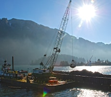 Corps contractors dredge sediment near Bonneville Dam. If not removed by dredging, sediment can enter a flow channel where it can settle inside the dam structure, where its removal is much more difficult.