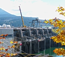 In the Willamette Valley, Dexter Dam's permanent gantry crane stands sentry as a mobile crane supports spillway gate repairs. The mobile crane lifts a new gate arm into place.