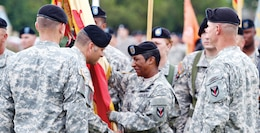 Col. Robert A. Law III, second from left, passes the 1st Sust. Bde.'s colors to Command Sgt. Major Tomeka O'Neal, second from right, entrusting her with responsibility of the unit and its Soldiers during a Change of Command and Change of Responsibility ceremony July 26 at Cavalry Parade Field.  Photo by: 1ST SUST. BDE.