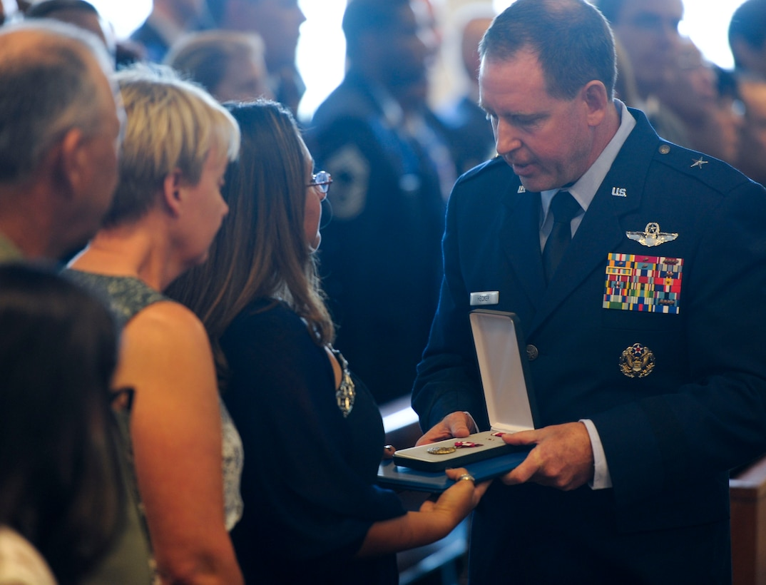 U.S. Air Force Brig. Gen. James Hecker, 18th Wing commander, presents a Meritorious Service Medal to Tech. Sgt. Mark Smith's spouse, Jessica, during a memorial service at Chapel One on Kadena Air Base, Japan, Aug. 13, 2013. The MSM was awarded to Smith posthumously. (U.S. Air Force photo by Airman 1st Class Justin Veazie/Released)