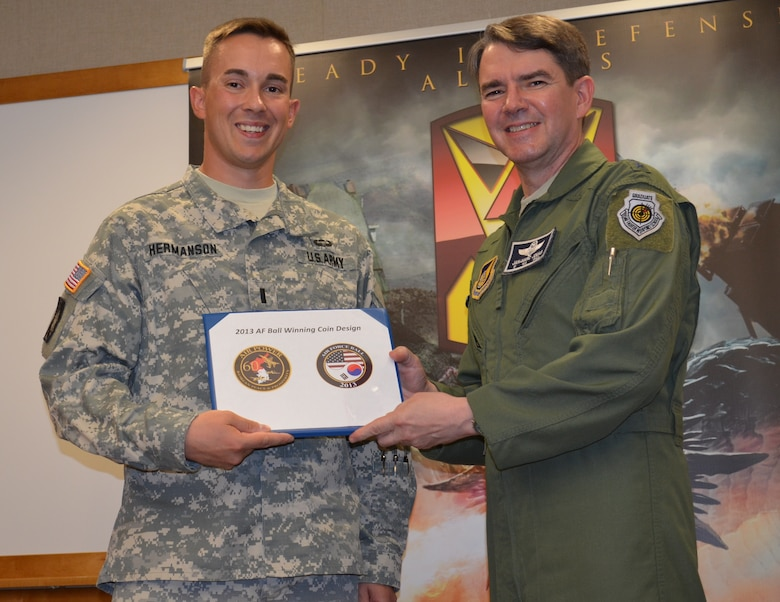 Lt. Gen.  Jan-Marc Jouas, commander of the 7th Air Force at Osan Air Base, poses with the winning coin design with 1st Lt.  Kyle Hermanson, executive officer with Battery B, 6th Battalion, 52nd Air Defense Artillery Regiment at Osan Air Base, Aug. 9. Hermanson is married to Allison Hermanson, a flight medic with the Air Force Individual Ready Reserve.  They are expecting their first child at the end of September. (U.S. Army Photo By Spc. Shawn Denham, PAO, 35th ADA.)