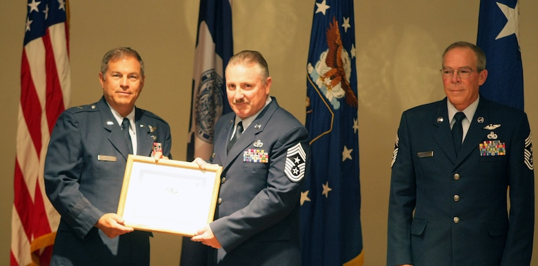 Chief Master Sgt. William G. Whipple accepts a certificate from Brig. Gen. Harold Reed, deputy adjutant general, and assumed position as the new State Command Chief for Wyoming at a transfer of authority ceremony conducted at the Joint Forces Readiness Center Aug. 3, 2013, in Cheyenne, Wyo. Whipple replaces Chief Master Sgt. Ralph D. Hensala (right) who formally retired after the ceremony. (U.S. Army National Guard Photo by Sgt. 1st Class James McGuire)