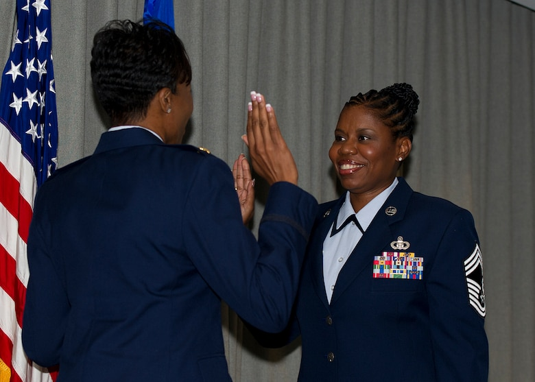 Chief Master Sgt. Jacinda Rivers, Air Force Special Operations Command command and control functional manager, right, raises her hand during her promotion ceremony to chief master sergeant during at ceremony at Hurlburt Field, Fla., July 27, 2012. The rank of chief master sergeant is limited by federal law to only one percent of the Air Force enlisted force. (U.S. Air Force photo / Airman 1st Class Christopher Callaway)