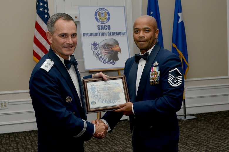 U.S. Air Force Maj. Gen. Jake Polumbo, 9th Air Force commander, receives a certificate of appreciation from Master Sgt. Demetrius Jones, Shaw Top 3 president, during a senior NCO induction ceremony, Shaw Air Force Base, S.C., Aug. 9, 2013. The ceremony was held to welcome new master sergeants to the senior enlisted tier. (U.S. Air Force photo by Airman 1st Class Ashley L. Gardner/Released)