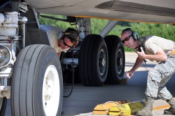507th Aircraft Maintenance Squadron crew chief Tech. Sgt. Richard Baker, left, helps Senior Airman Matthew Dobbins of the Oklahoma Air National Guard 137th Air Refueling Wing pull chalks on a departing KC-135 Stratotanker.  Baker trains Dobbins on pre-flight and take-off procedures.  Integrating guard/reserve Airman on the flight line for aircraft launch and recovery is a unique opportunity to demonstrate the seamless guard/reserve association here.  (U.S. Air Force photo/Senior Airman Mark Hybers)
