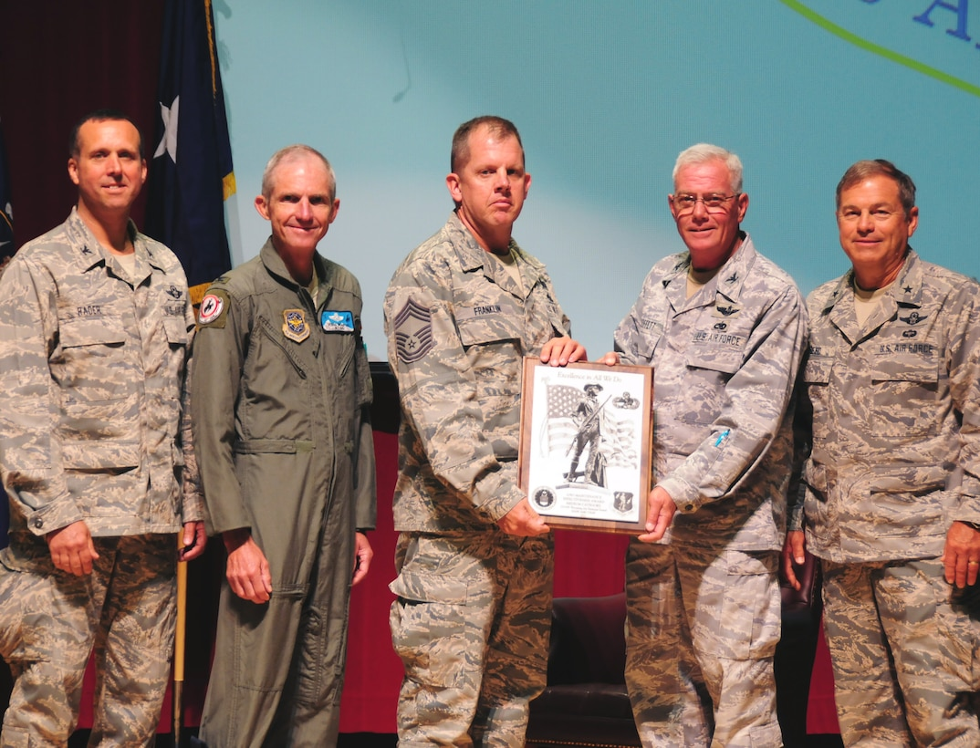 """Col. James """"Pat"""" Moffett, 153rd Maintenance Group commander, and Chief Master Sgt. Douglas Franklin, chief  of maintenance operations, accept the Air National Guard's 2012 Maintenance Effectiveness Award in the medium category from Brig. Gen. Harold Reed (right), deputy adjutant general, Col. Dennis D. Grunstad II, assistant adjutant general-air, and Col. Stephen Rader (left), 153rd Airlift Wing commander, on August 2, 2013 at Central High School in Cheyenne, Wyo. (U.S. Air National Guard photo by Staff Sgt. John Galvin)"""