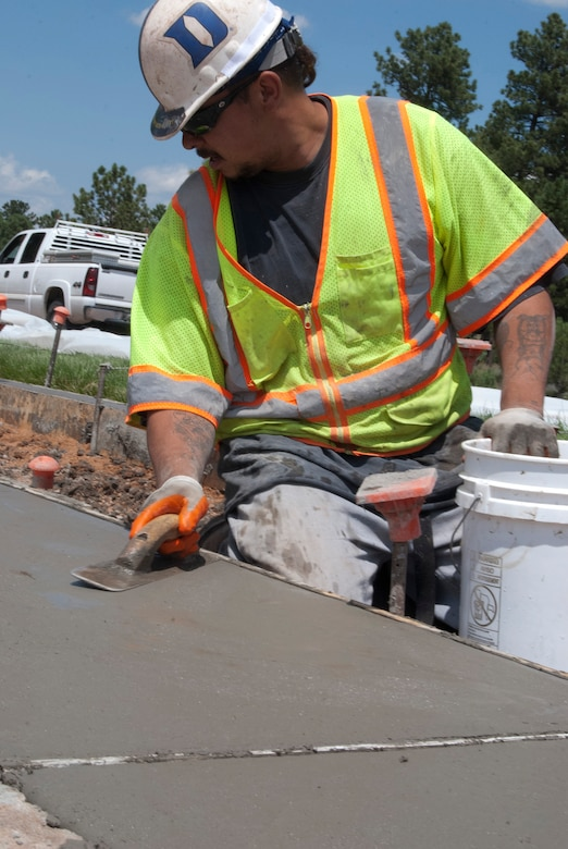 Gary Garcia smooths concrete on a median along Stadium Boulevard at the Air Force Academy Aug. 9, 2013. The 10th Civil Engineer Squadron is using the median as a test to determine the cost and savings of Xeriscaping instead of replacing strips of grass along the median every year. Garcia is an employee of Cosyleon and Cosyleon, a contractor based in Pueblo, Colo., that specializes in concrete placement. (U.S. Air Force photo/Don Branum)
