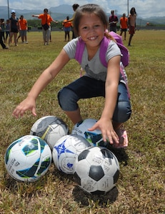 """During an event here, hosted by the Medical Element called Fiesta Day, a young girl poses with soccer balls donated by """"Kick for Nick"""" Aug. 10, 2013. The JTF-Bravo's MEDEL joined with """"Kick for Nick,"""" a nonprofit organization, to hold a Fiesta Day, during the event, more than 75 girls from a local orphanage received more than 35 soccer balls donated by the organization, while also participating in other activities. (Photo  released by U.S. Air Force Staff Sgt. Jarrod Chavana)"""