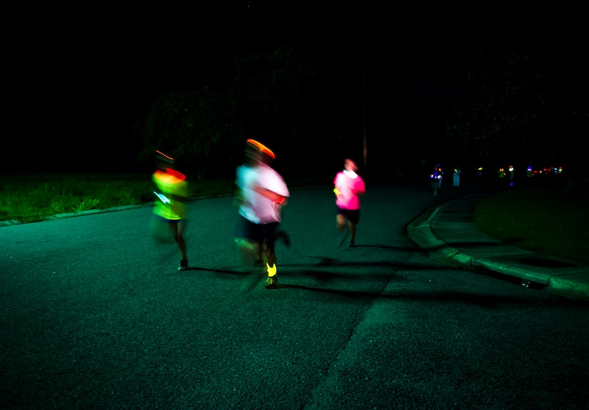 Service members and their families run through base housing wearing glow-in-the-dark clothing and accessories during the Nuclear Glow 5K Aug. 9, 2013, at Joint Base Charleston – Weapons Station, S.C. The race was hosted by the 628th Force Support Squadron. (U.S. Air Force photo/ Senior Airman Dennis Sloan)