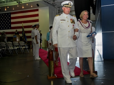 """Capt. Thomas Bailey, Joint Base Charleston deputy commander and former Naval Weapons Station commanding officer and his wife Janet, are piped ashore at the conclusion of his retirement ceremony Aug. 9, 2013, aboard the USS Yorktown (CV 10) at Patriots Point Naval and Maritime Museum, Mount Pleasant, S.C. """"Piping Ashore"""" is a historical and traditional naval ceremony that began in the 1700's. Traditionally, the retiree requests permission to """"go ashore"""" for the last time, symbolizing the end of a naval career. Bailey served more than 30 years in the U.S. Navy. (U.S. Air Force photo/Tech. Sgt. Rasheen Douglas)"""