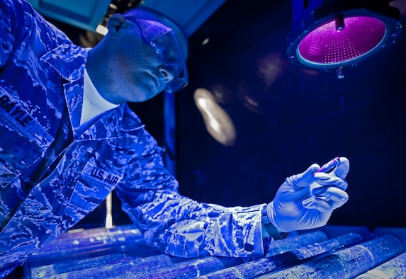 Staff Sgt. David Bayle inspects an aircraft pin for cracks under a black light after dipping the part into chemicals mixed to show cracks not normally visible to the naked eye at the 379th Air Expeditionary Wing in Southwest Asia, Aug. 6, 2013. Bayle is a 379th Expeditionary Maintenance Squadron nondestructive inspection craftsman deployed from Eielson Air Force Base, Alaska, and hails from Port Sanilac, Mich. (U.S. Air Force photo/Senior Airman Benjamin Stratton)