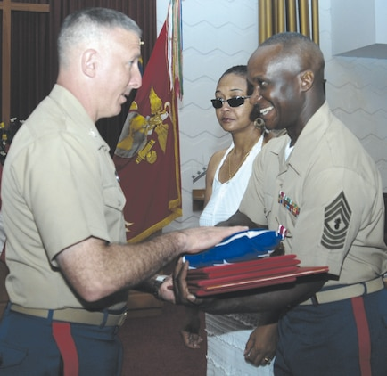 Master Gunnery Sgt. Terry Cooper, right, senior enlisted advisor and logistics chief for the Operations Directorate, Marine Corps Logistics Command, receives an American flag, a certificate of retirement and several letters commending his service Aug. 9 from Col. Don Davis, commanding officer, Marine Corps Logistics Base Albany during a retirement ceremony held at the Base Chapel.