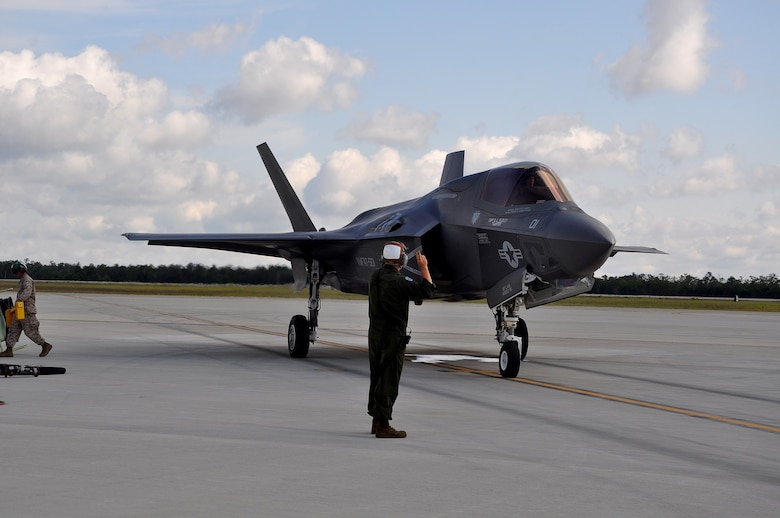 """A U.S. Marine Corps plane captain, known as a crew chief in the Air Force, marshals out an F-35B Lightning II short takeoff and vertical landing variant of the aircraft May 22, 2013, at Eglin Air Force Base. The maintainer orchestrated a """"hot pit"""" ground refueling, running the engine while receiving fuel, allowing it to take off immediately afterward for another training sortie. Assigned to the Marine Fighter Attack Training Squadron-501, the plane captain helped train up 24 U.S. and United Kingdom pilots flying the B variant to date by having aircraft ready for the daily flight operations."""