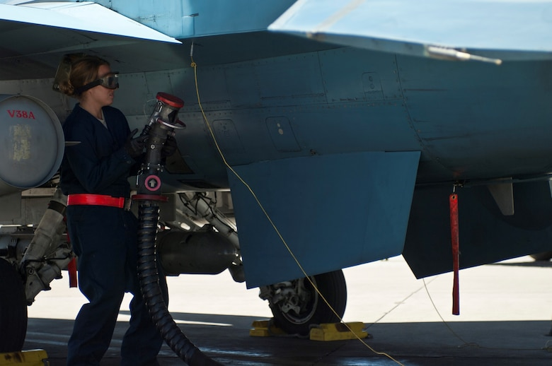 Staff Sgt. Chelsea Mays disconnects a fuel hose as part of preflight preparations for a 64th Aggressor Squadron F-16 Fighting Falcon Aug. 13, 2013, at Nellis Air Force Base, Nev. It is the crew chief's responsibility to ensure the aircraft is properly refueled before each training mission.  Mays is a F-16 crew chief assigned to the 926th Aircraft Maintenance Squadron. (U.S. Air Force photo/Airman 1st Class Joshua Kleinholz)