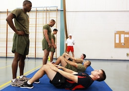 Marines with Marine Rotational Force - Darwin and Australian soldiers conduct 100 situps to a cadence during a Combat Fitness Leadership Course Barrier Test at the Northern Gym, here, July 30. This was one of seven different exercises participants had to complete. The top two Marine performers in the barrier test will attend the month-long CFLC.