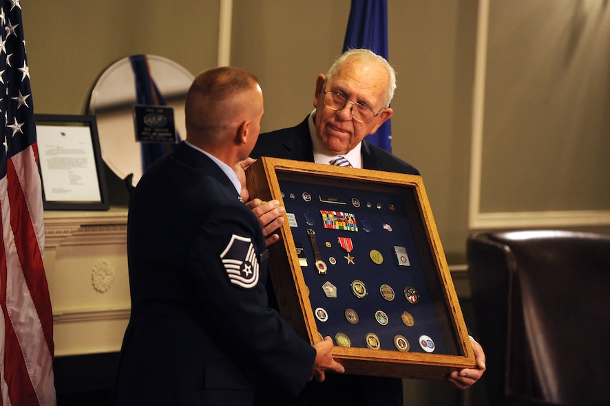 James Norwood, an electronic intelligence advisor with the National Security Agency's representative office at United States Strategic Command, receives a shadow box from U.S. Air Force Master Sgt. William Bonen, superintendent cryptologic service group with USSTRATCOM, at a retirement ceremony held at the Patriot Club July 31 on Offutt Air Force Base, Neb.  The nearly 60 years of combined enlisted and civil service medals and trinkets adorned the shadow box which is usually given to military retirees.  (U.S. Air Force photo by Josh Plueger/Released)