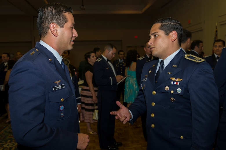Capt. Carlos Monroy (left), Colombia air force internal control offi cer, talks with Capt. Daniel Yapor, Dominican Republic air force pilot, after the Inter-American Air Forces Academy graduation banquet July 31. Monroy and Yapor met through the IAAFA  International Squadron Officers School Professional Military Education class at Joint Base San Antonio-Lackland.